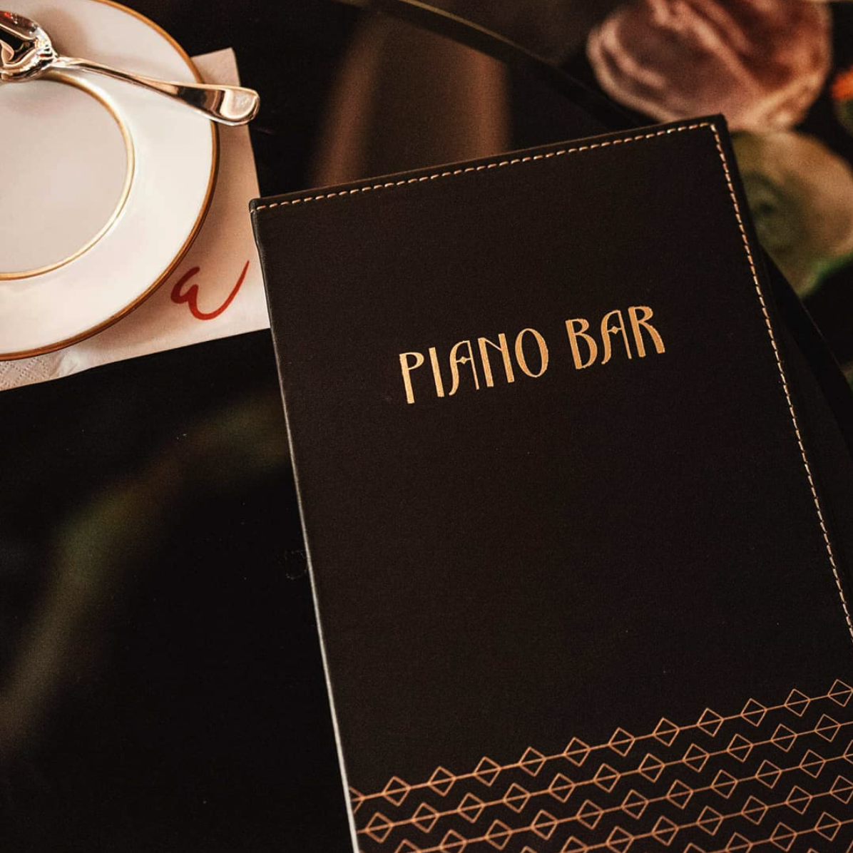 Piano Bar in gold lettering on a menu